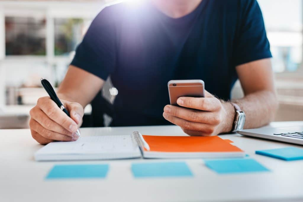 Close up shot of a man taking down note in a personal organizer with mobile phone in other hand. Young man hands working at his desk.